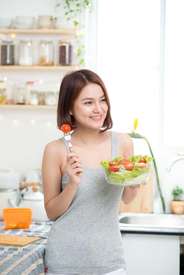 Menina asiática nova bonita que come a salada eati feliz de sorriso da menina imagem de stock