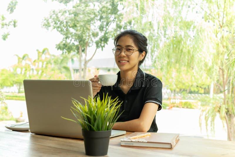 Menina asiática nova bonita que guarda o café com o portátil na tabela no café fotografia de stock