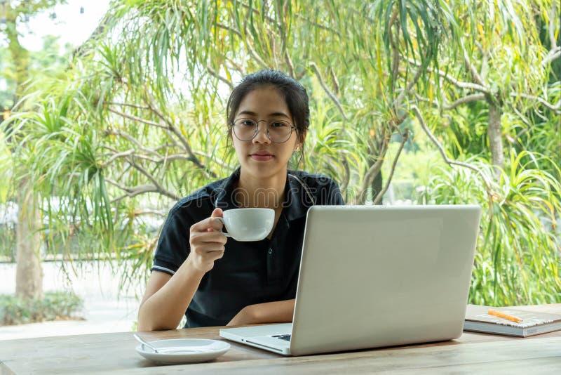 Menina asiática nova bonita que guarda o café com o portátil na tabela no café imagem de stock