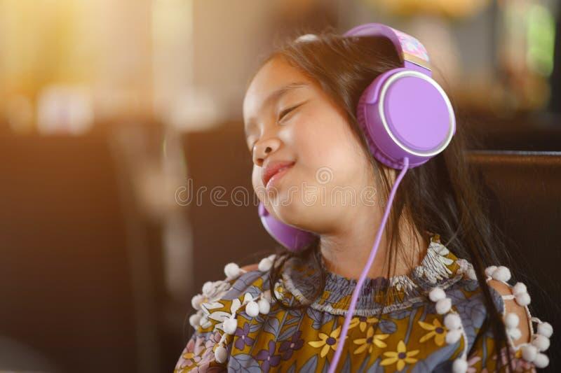 A menina asiática nova do estilo de vida relaxa a escuta a música na casa fotografia de stock