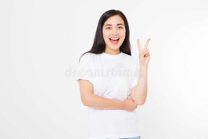 Menina asiática nova feliz que mostra o sinal da vitória isolado no fundo branco Copie o espaço Molde e camisa vazia do verão t fotografia de stock royalty free