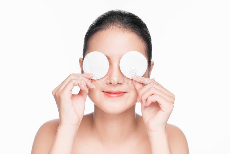 A menina asiática nova importa-se com o abrandamento da pele da cara usando a almofada de algodão imagens de stock