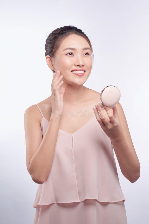 Menina asiática nova que faz a composição, aplicando o ruge a seu mordente fotos de stock