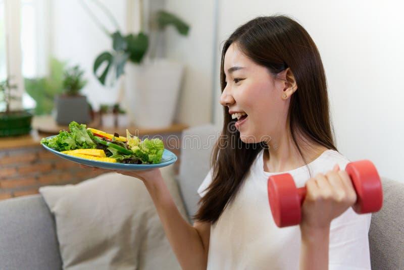 A menina asiática nova que guarda a salada e o peso vermelho está sentando-se no sofá com cara do sorriso fotografia de stock