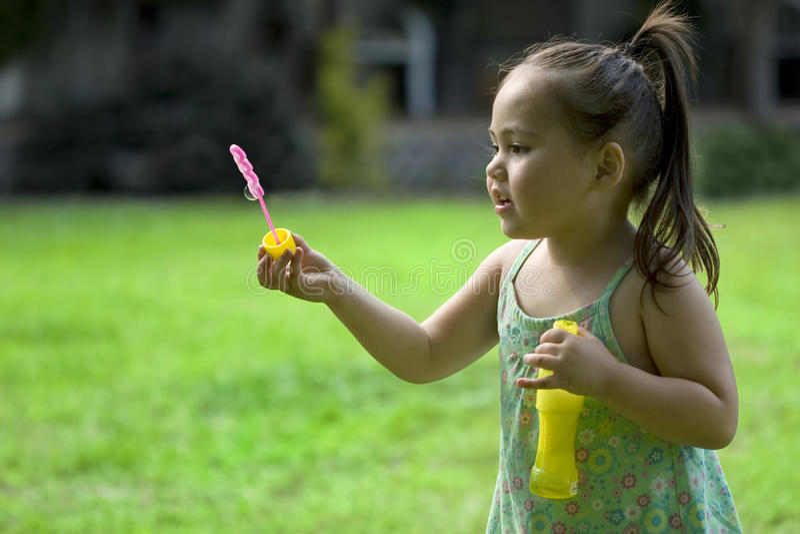 Menina asiática nova que joga com bolhas fotografia de stock royalty free