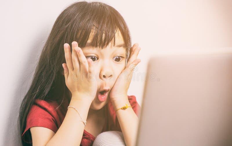 A menina asiática pequena é choque com o que vê no Internet foto de stock royalty free