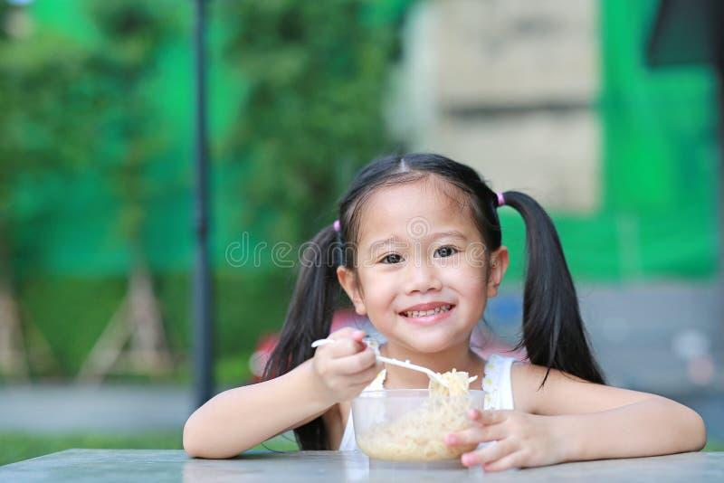 Menina asiática pequena adorável da criança que come macarronetes imediatos na manhã no jardim imagem de stock royalty free