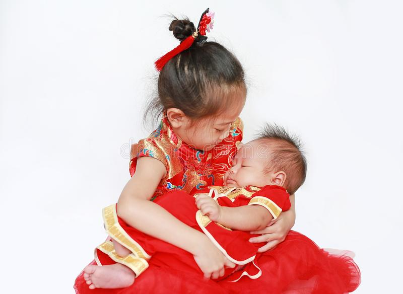 Menina asiática pequena adorável e bebê infantil no cheongsam isolado no fundo branco durante o ano novo chinês tradicional fotografia de stock royalty free