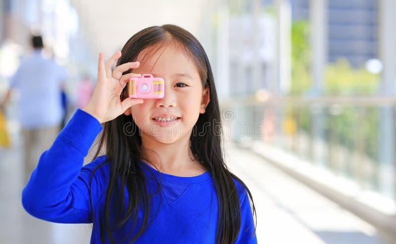 Menina asiática pequena adorável que usa uma câmera do brinquedo para tomar as imagens exteriores Conceito do desenvolvimento da  imagens de stock