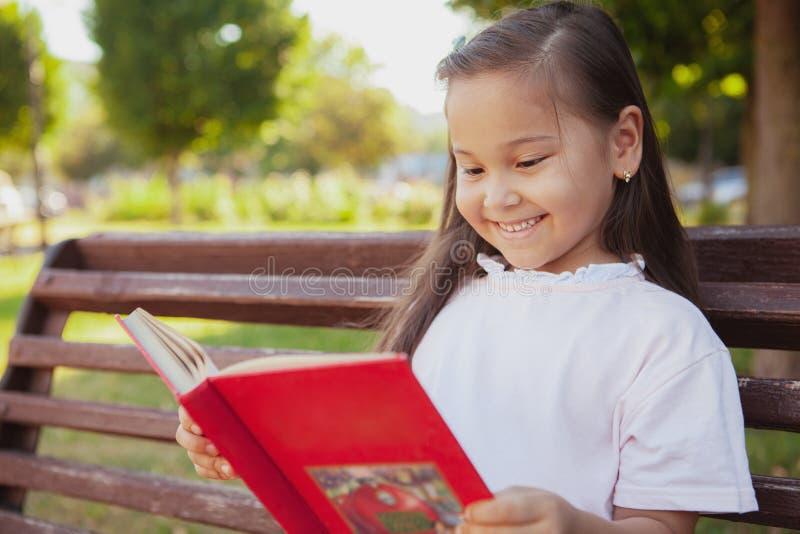 Menina asiática pequena bonita no parque em um dia de verão imagem de stock royalty free