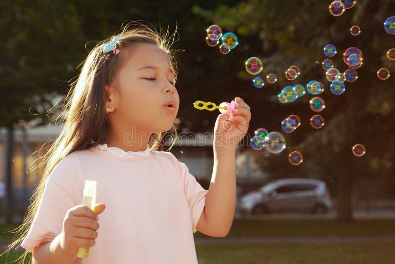 Menina asiática pequena bonita no parque em um dia de verão imagem de stock