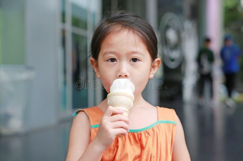 A menina asiática pequena bonito da criança aprecia comer o cone de gelado foto de stock royalty free