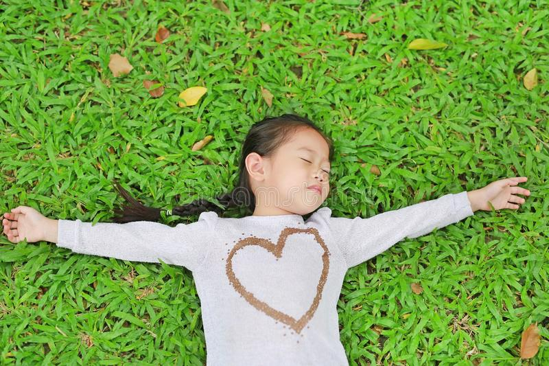 Menina asiática pequena bonito feliz da criança que encontra-se no gramado verde Sorrindo e fechado seus olhos imagem de stock