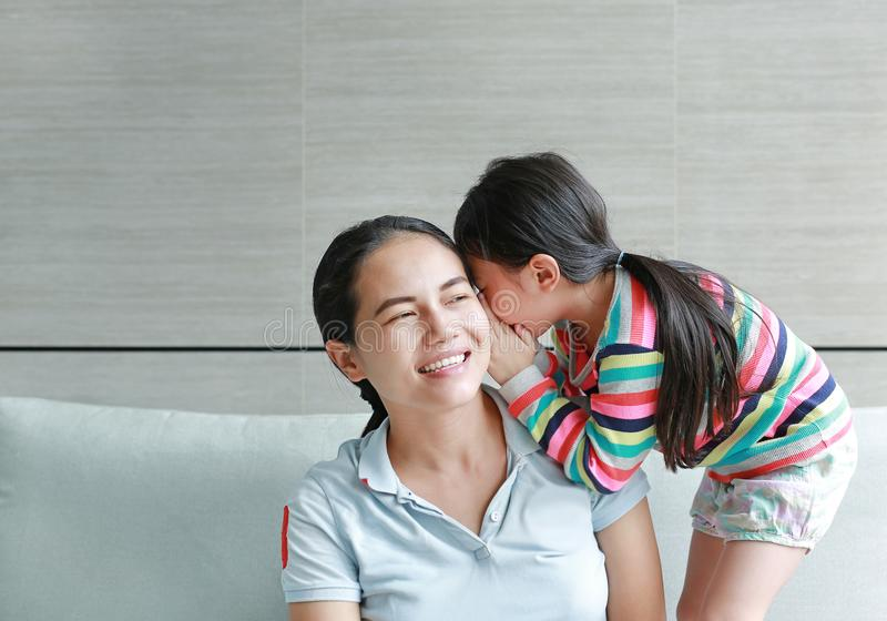 Menina asiática pequena bonito feliz da criança que sussurra um segredo a sua orelha nova das mães em casa Família e conceito dos fotografia de stock
