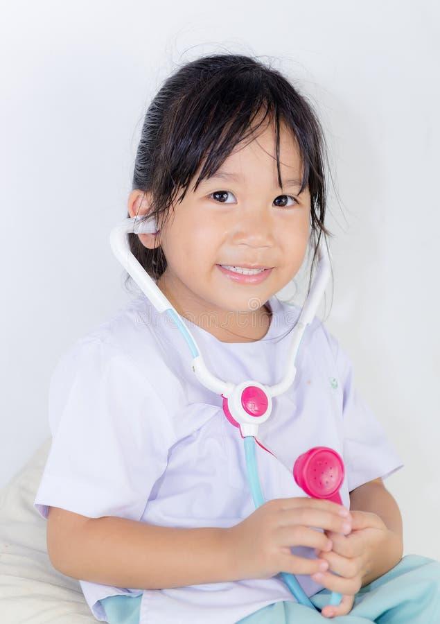 Menina asiática pequena bonito no traje do doutor imagens de stock