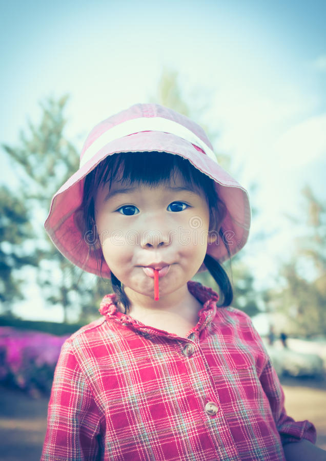 Menina asiática pequena bonito que come um pirulito no fundo da natureza dentro imagens de stock royalty free