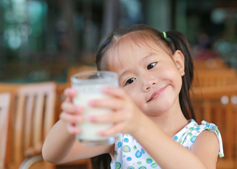 Menina asiática pequena bonito que guarda o vidro do leite na cafetaria foto de stock