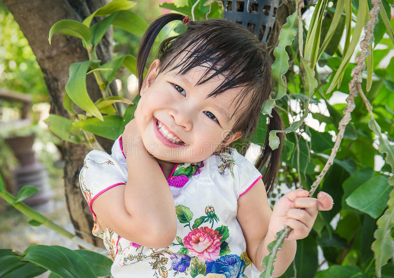 Menina asiática pequena bonito que veste o terno chinês no parque imagens de stock royalty free