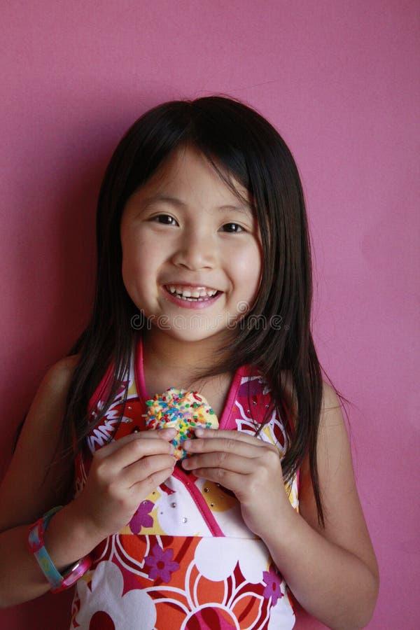 Menina asiática pequena com bolinho imagens de stock royalty free