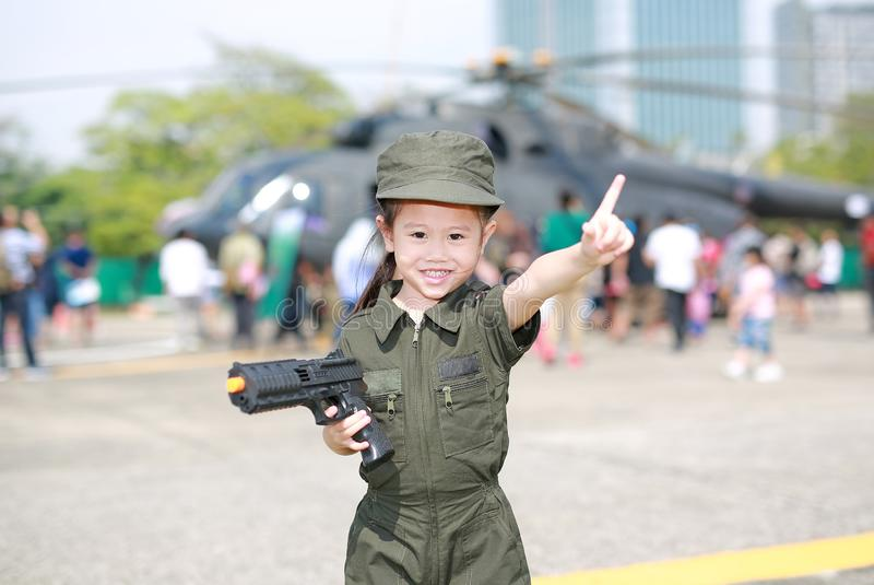 Menina asiática pequena da criança no traje piloto do terno do soldado com arma da terra arrendada à disposição e apontando acima imagens de stock