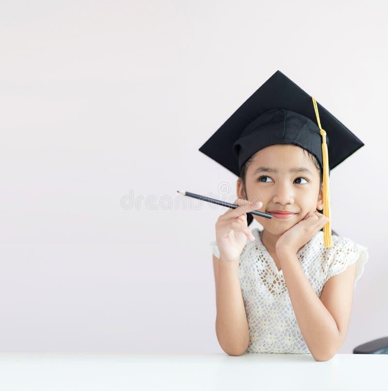 A menina asiática pequena do retrato está vestindo o lápis graduado da terra arrendada do chapéu que senta-se pensando algo e o s fotografia de stock