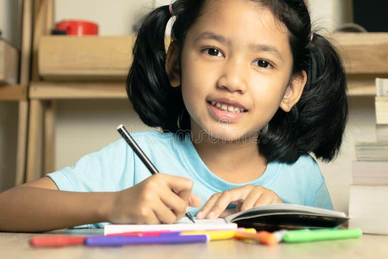 A menina asiática pequena está escrevendo um livro foto de stock royalty free