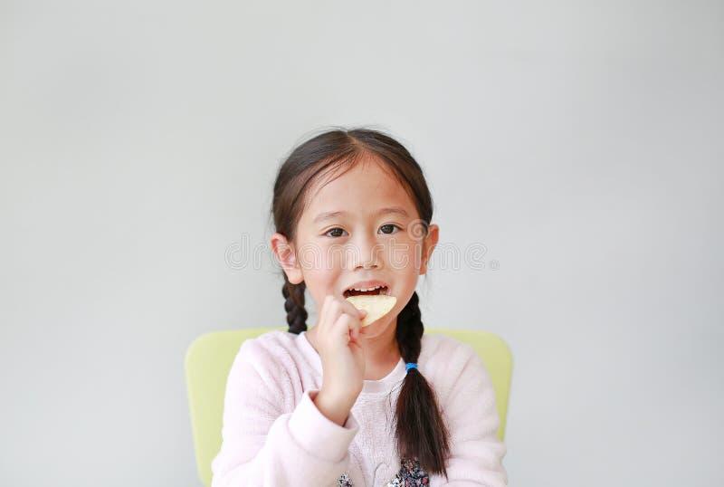 Menina asiática pequena feliz adorável da criança que come microplaquetas de batata friáveis no fundo branco A criança aprecia co fotografia de stock royalty free