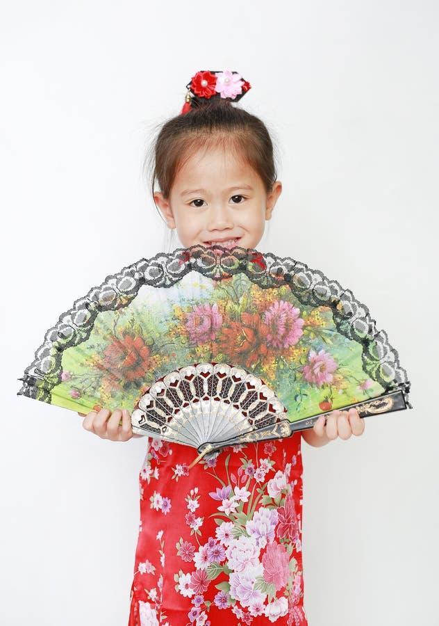 Menina asiática pequena feliz da criança que guarda o fã do estilo chinês no fundo branco durante o festival chinês do ano novo imagem de stock royalty free