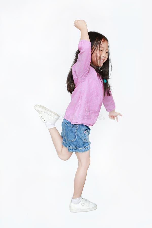 Menina asiática pequena feliz da criança que salta no ar no fundo branco Ideia lateral do comprimento completo do conceito de sor fotografia de stock
