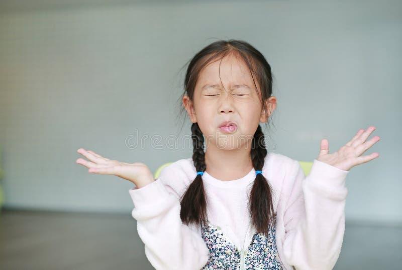 Menina asiática pequena irritada da criança na sala de aula N?o escutando Conceito do sinal e do gesto imagens de stock