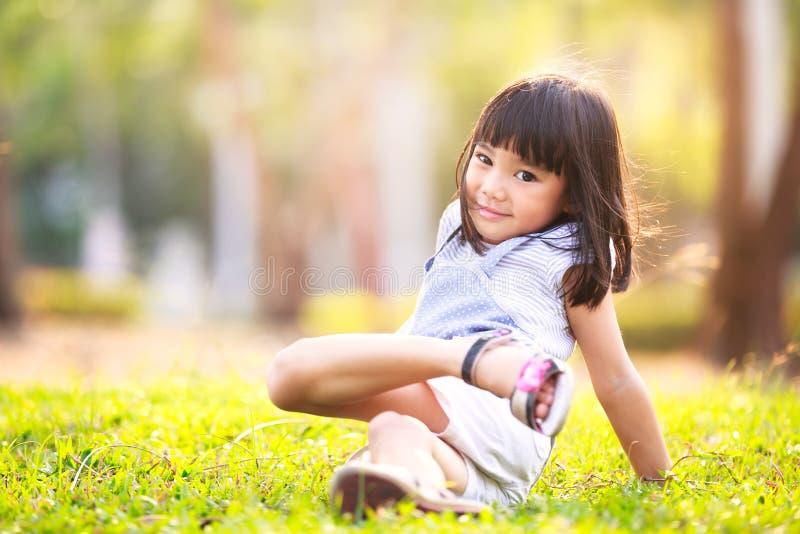Menina asiática pequena na grama no jardim fotografia de stock
