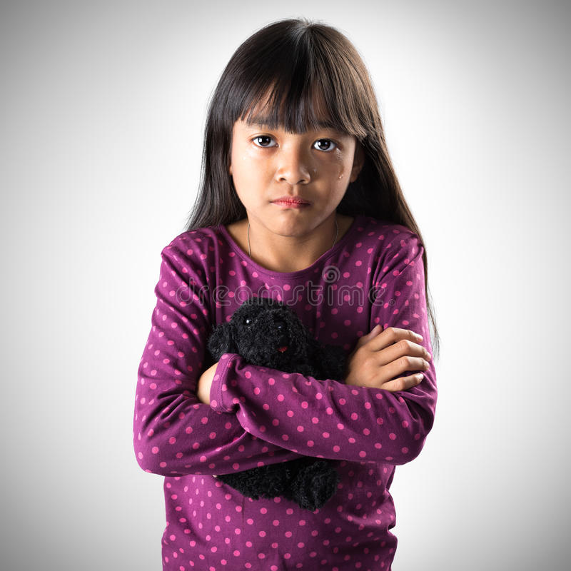 Menina asiática pequena que grita com os rasgos que rolam para baixo seus mordentes foto de stock