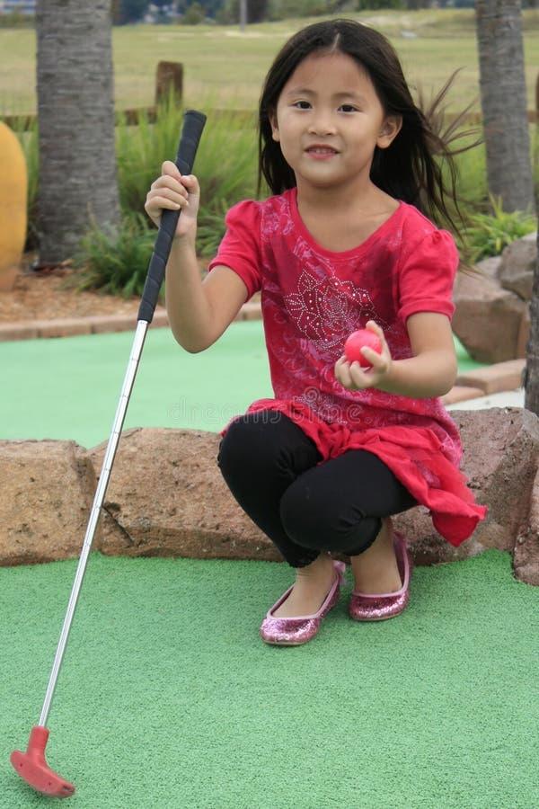 Menina asiática pequena que joga o mini golfe fotografia de stock royalty free