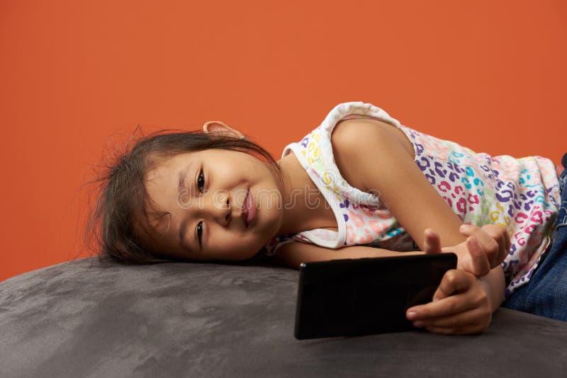 Menina asiática pequena que usa o smartphone fotografia de stock