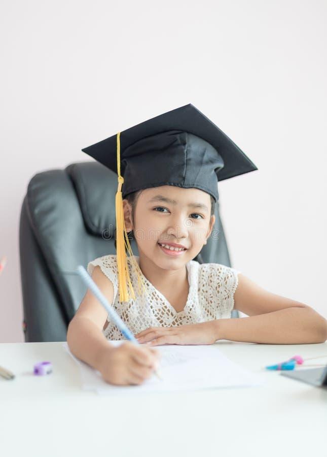 Menina asiática pequena que veste o chapéu graduado que faz trabalhos de casa e sorriso com felicidade para o sucesso do foco sel imagens de stock