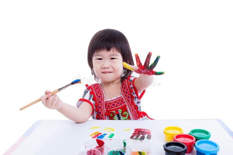 A menina asiática pinta sua mão, conceito da faculdade criadora Isolado no branco fotos de stock royalty free