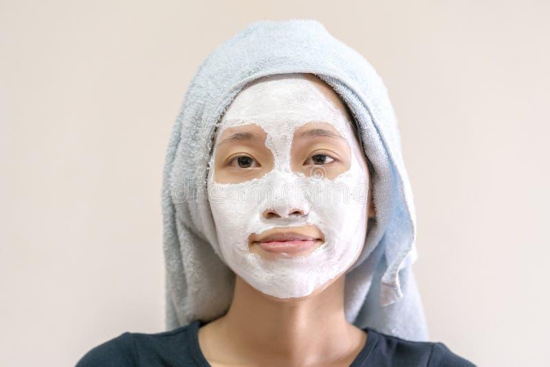 Menina asiática que aplica a máscara de creme facial imagem de stock royalty free