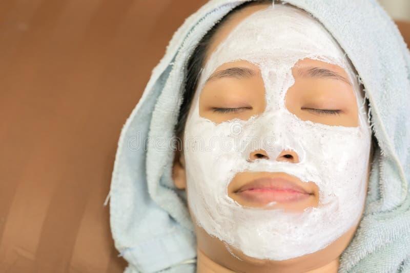 Menina asiática que aplica a máscara de creme facial imagens de stock