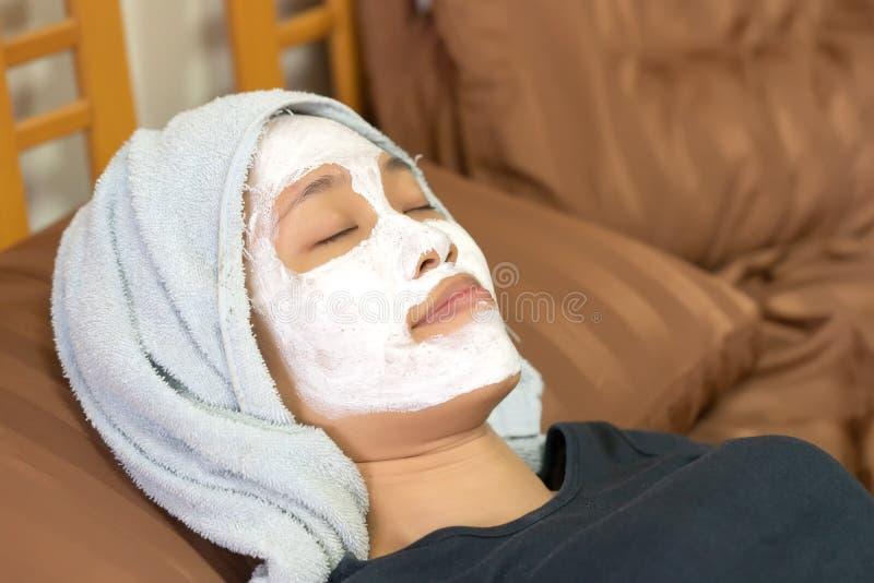 Menina asiática que aplica a máscara de creme facial foto de stock royalty free