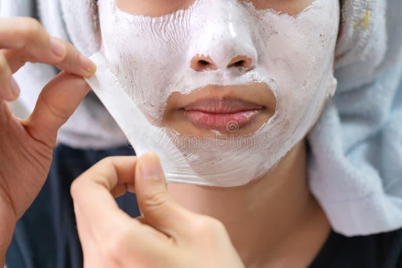 Menina asiática que aplica a máscara de creme facial fotos de stock