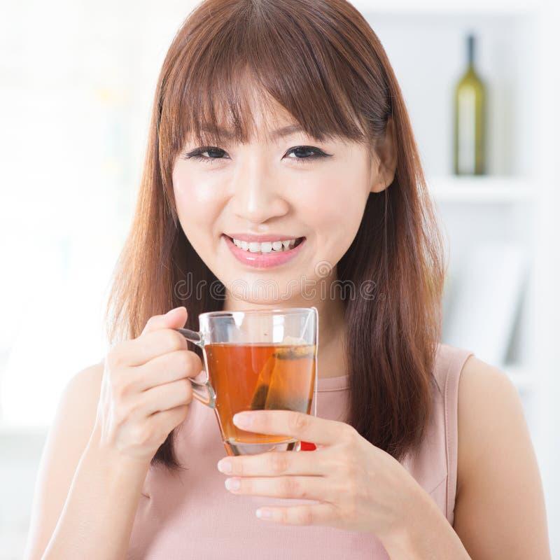 Menina asiática que aprecia o chá fotografia de stock