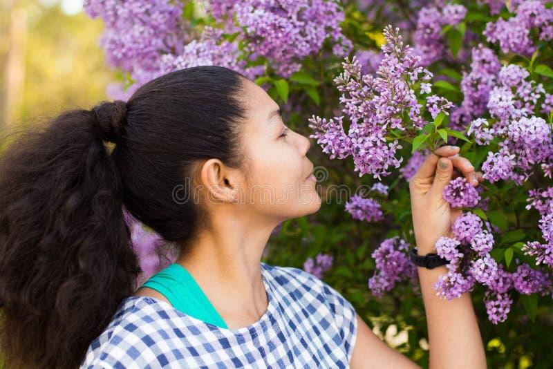 Menina asiática que cheira as flores imagem de stock