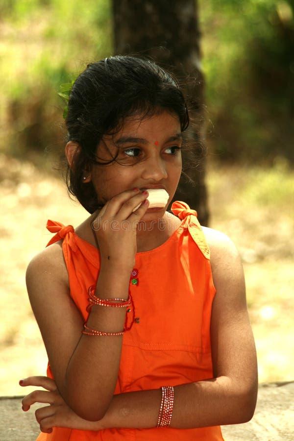 Menina asiática que come a banana imagem de stock