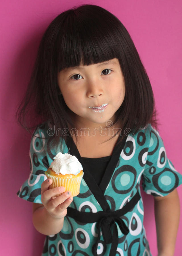 Menina asiática que come o queque imagem de stock