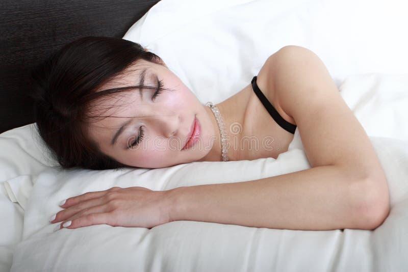 Menina asiática que dorme na cama imagem de stock