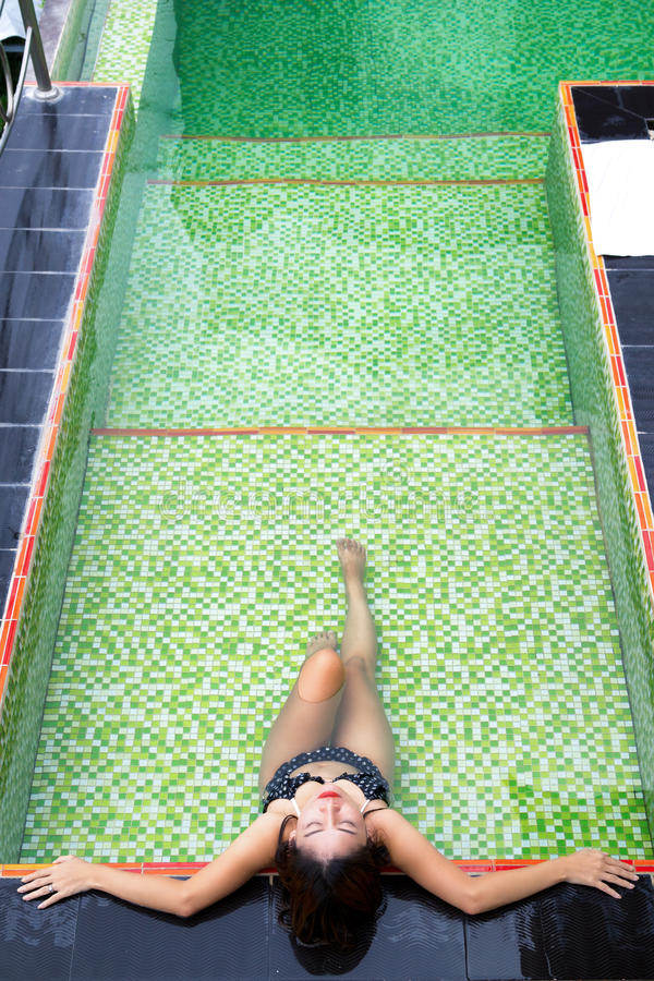 Menina asiática que encontra-se na piscina foto de stock