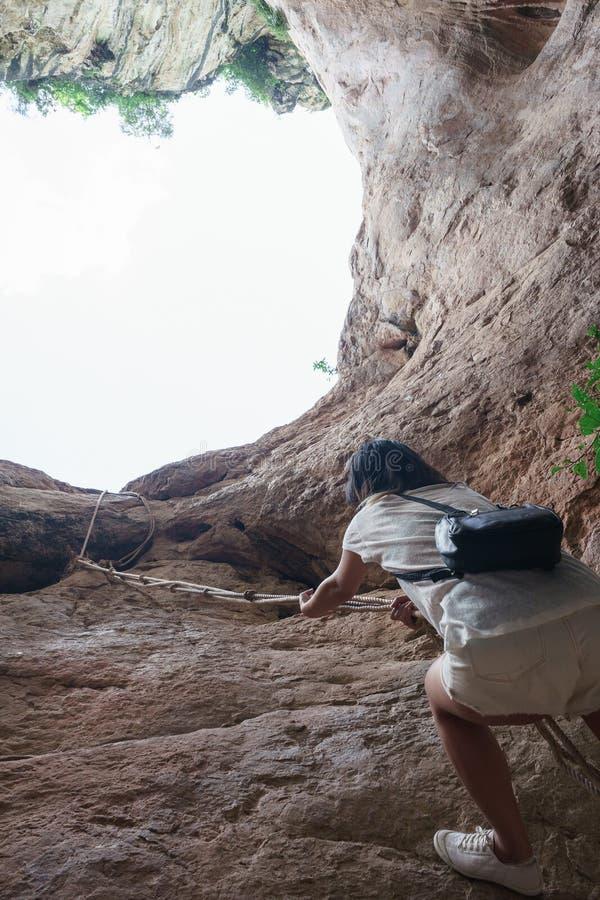 Menina asiática que escala acima a corda no penhasco rochoso fotografia de stock royalty free