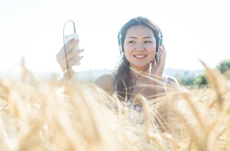 Menina asiática que escuta a música no trigo foto de stock royalty free