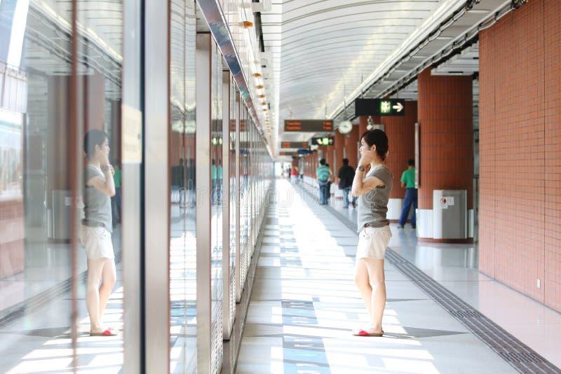 Menina asiática que espera no estação de caminhos-de-ferro foto de stock