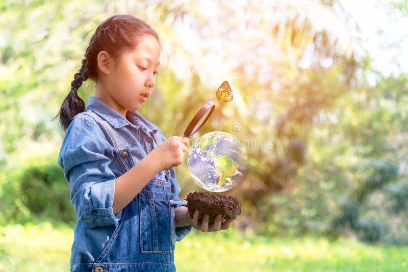 Menina asiática que guarda a lupa que encontra plantas do crescimento no mundo verde imagens de stock royalty free